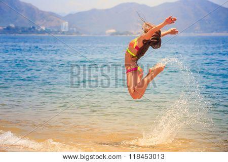 Blonde Slim Girl In Bikini In Jump Over Sea Splashes