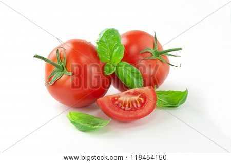 Whole Tomato With A Slice Of Tomato And Basil Leaves
