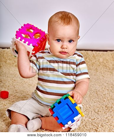 Kid baby boy sitting on floor and plying with puzzle toy at home.