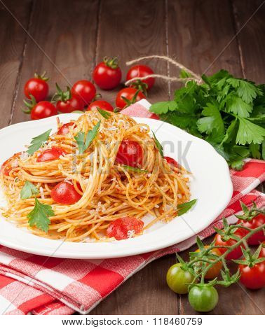 Spaghetti pasta with tomatoes and parsley on wooden table. View with copy space