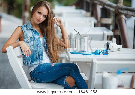 Young beautiful woman at a table in summer cafe