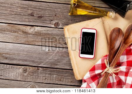 Kitchen table with ingredients, utensils and smartphone with blank screen for your app over cooking book on wooden table. Top view with copy space