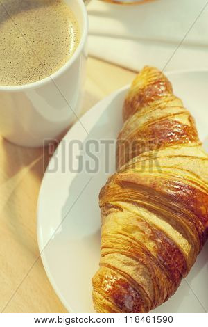 Instagram filter style photograph of a breakfast croissant and cup of hot coffee illuminated by golden early morning sunshine