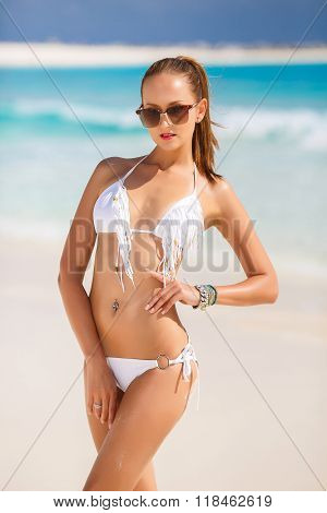 The young attractive woman in bikini on a beach
