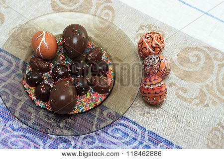 Handmade Colorful Painted Easter Egg With Chocolate Candies And Eggs Against Matching Tablecloth