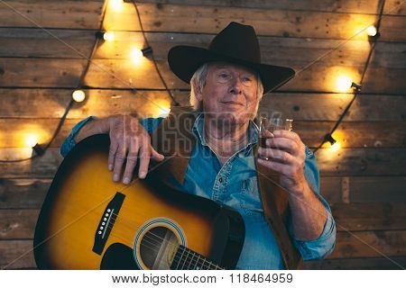 Country And Western Musician Sitting With Guitar. Having A Drink.