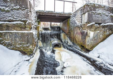 Concrete River Dam With Non-freezing Water Stream In Winter