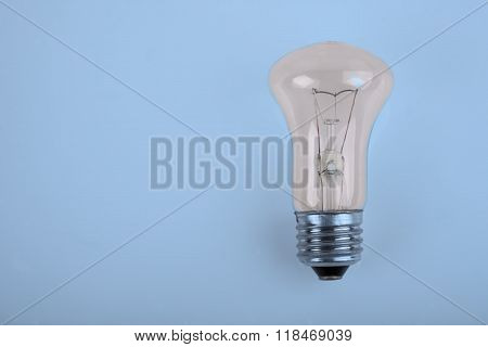 traditional incandescent light bulb on blue background