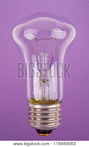 traditional incandescent light bulb on blue purple background