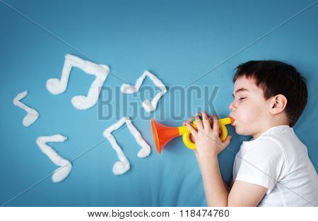 boy on blue blanket background with pipe