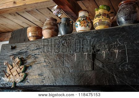 Painted mugs as decoration on an old press in the wine cellar