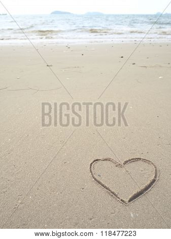 Heart-shape drawing right-side on the sandy beach with sea background
