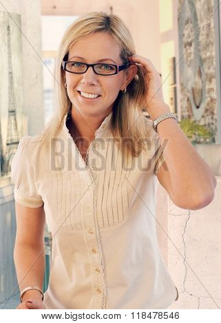 Portrait of happy casual caucasian blonde mid adult woman at home. Smiling, wearing glasses, looking at camera, hand in hair.