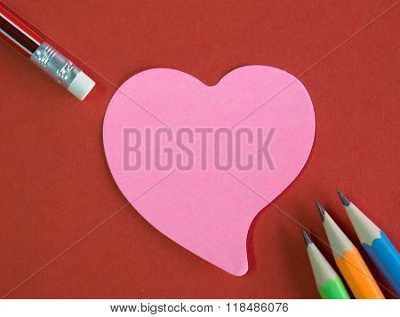 Pink Heart-shaped Memorandum On Red Paper With Colorful Pencils And Eraser