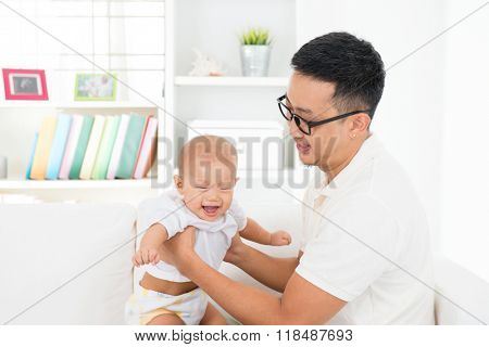 Happy father and baby boy playing at home. Southeast Asian family lifestyle indoors.