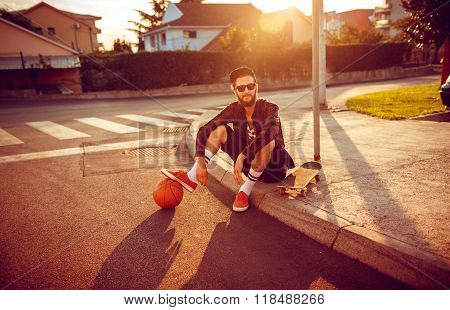 Young Stylish Man With A Basketball And Skateboard Sitting On A City Street At Sunset Light