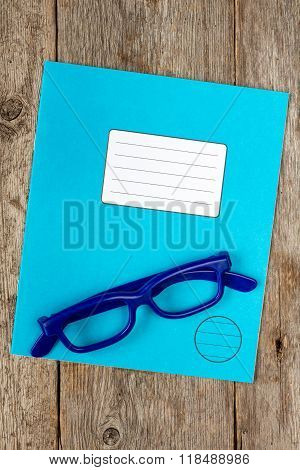 Blue Exercise Book And Glasses