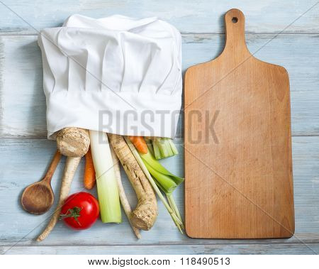 Vegetables in chef's hat and empty cutting board