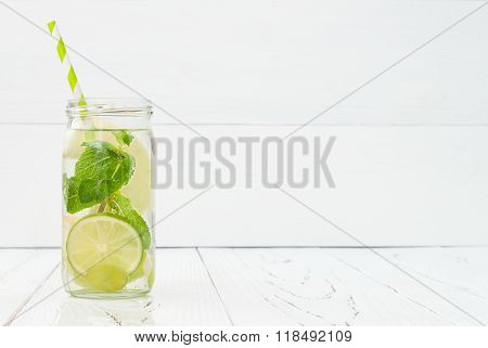 Refreshing homemade lime and mint cocktail over old vintage wooden table. Detox fruit infused flavor