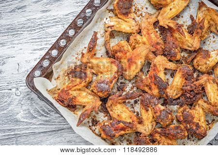 Roasted Chicken Wings On A Baking Tray On A Wooden Table, Top View. Copy Space