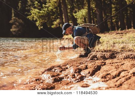 Mature Man Washing Face From Lake Water