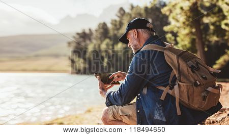 Mature Man On Hike In Nature Using Digital Tablet