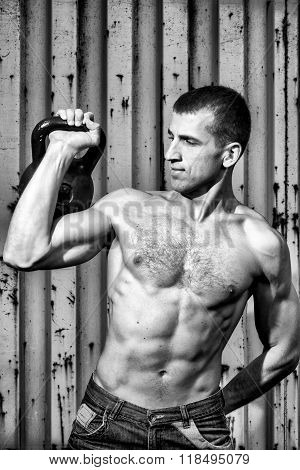 Young Athlete Man Doing Workout With Heavy Weights On The Background Of A Gray Metal Wall