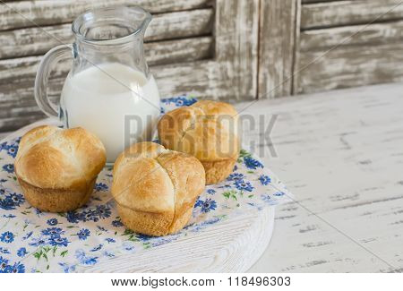 Homemade Sweet Brioche Rolls And A Pitcher Of Milk On A Light Rustic Wood Background