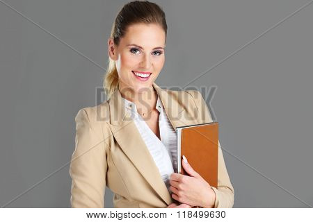 Picture of businesswoman with agenda over grey background