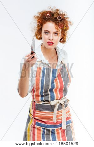 Beautiful housewife holding knife isolated on a white background