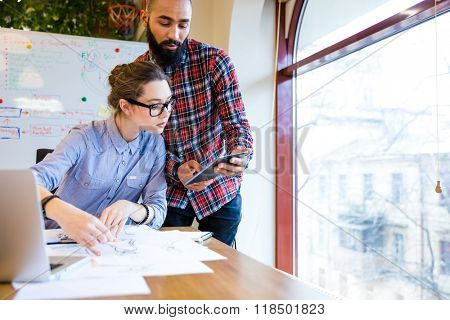 Two young woman and man fashion designers working and using tablet together
