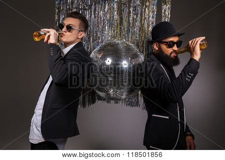 Two handsome confident young men in black suits and sunglasses standing near disco ball and drinking beer over black background