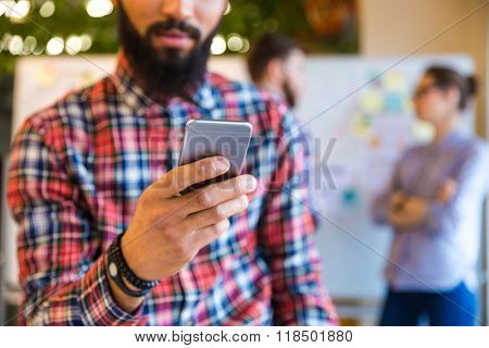 Cropped image of afro american man using smartphone in office with colleagues on background