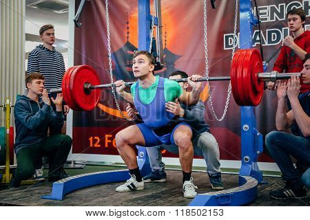 young athlete of powerlifter squats barbell