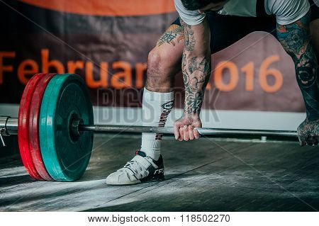 young athlete with tattoo performs deadlift barbell