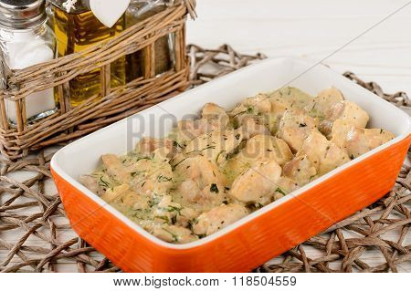 Chicken meat baked with bechamel sauce on wooden table.