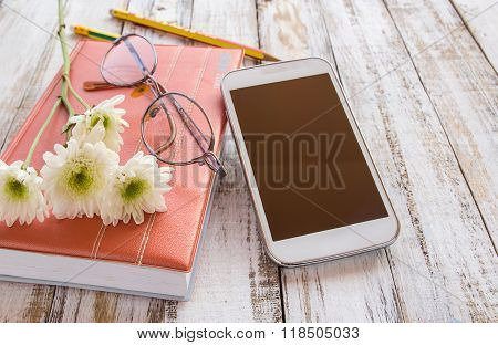 White Flower And Pencil On Notebook With Smartphone On Wooden Table