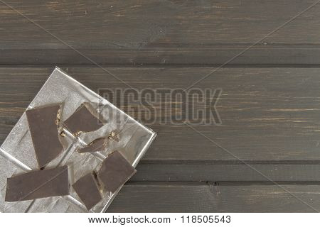 Chocolate wrapped in aluminum foil on a dark wooden board.