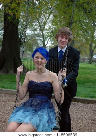 Young happy, smiling, attractive teen couple pose outdoors on swing set for prom photo.