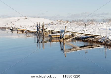 Small Wodden Bridges Reflecting In The Water In The Wintry Archipelago
