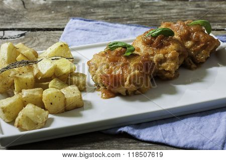 cod fish with tomato sauce and deep fried potato on tray