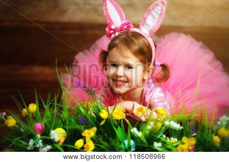 Happy Child Girl In  Costume Easter Bunny Rabbit On Grass And Flowers
