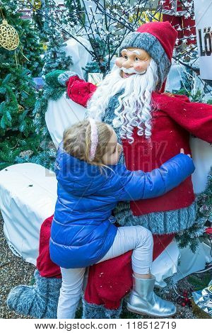 Cute Blond Girl, 4 Years Old, With Pink Hoop In Her Hair  And  Blue Coat Near Santa Claus