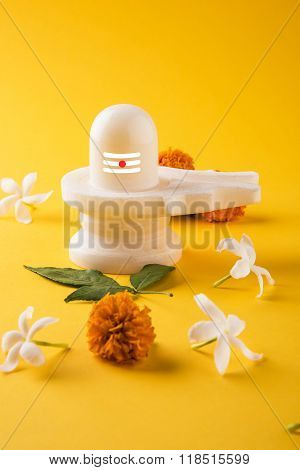 Shiva Linga made up of white marble decorated with flowers & bael leaf known as Aegle marmelos, maha