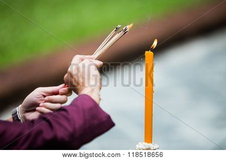 Man And Woman Hand Lighting Candles In A Church