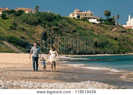 Happy Family Walking On The Coast In Spain