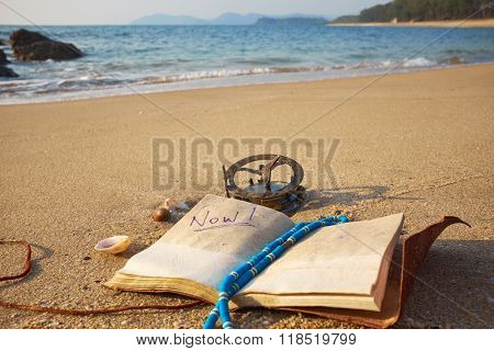 panorama of tropical beach with old vintage sundial and notebook