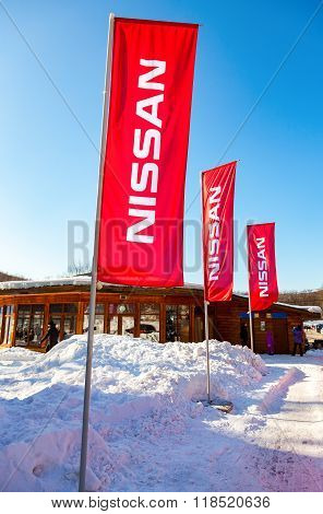 Dealership Flags Nissan Over Blue Sky In Sunny Day