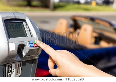 Hand Selecting Time On Parking Meter With Convertible Car In Background