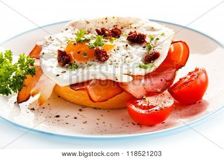 Breakfast - bread roll, fried egg, bacon and vegetables